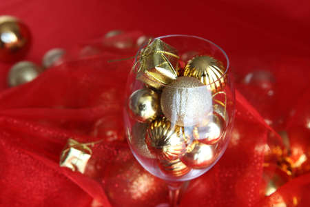 Christmas background with vine glass and gold christmas decorations inside it. vine glass with christmas decorations
