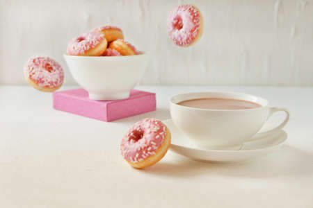 Flying pink donuts with a cup of cacao on a white background. selective focus on pink flying donuts 免版税图像