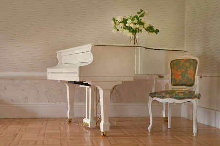 white grand piano standing in elegant white interior of palace hall.white piano at the empty reto room Imagens