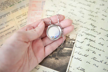 woman hand holding beautiful luxury round locket on letters and photo background. emories concept. locket on the woman hand