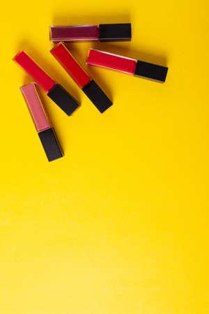 female bright lipsticks on mono colour yellow background
