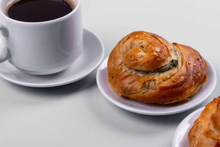 a cup of espresso and a cinnamon roll