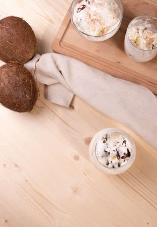 delicious creamy milky vanilla ice cream with caramel and chocolate addings in a glass container on the light rustic background