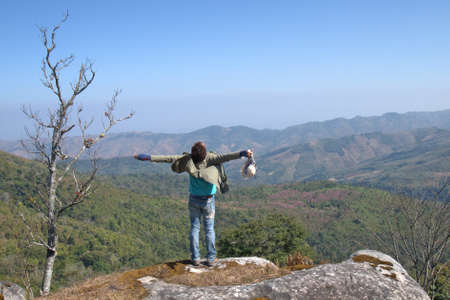 valley below: Happy guys standing on a rock with raised hands and looking at the valley below in Phu Lom Lo mountain, Loei, Thailand. Stock Photo