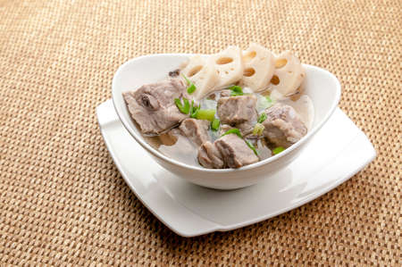 A white porcelain bowl with a bamboo woven background is filled with healthy, nutritious and delicious lotus root ribs soup, sprinkled with green onions on top to add flavor and vision Banco de Imagens