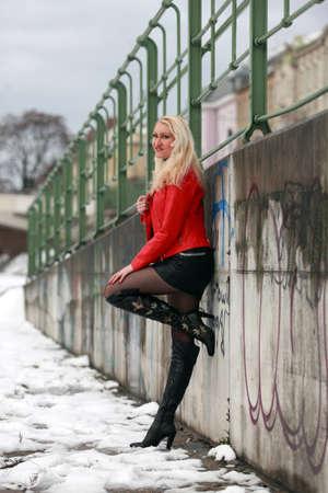 mini skirt: Belle femme blonde en veste de cuir rouge et mini jupe