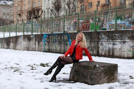 minifalda: Mujer rubia hermosa en la chaqueta de cuero rojo y mini falda