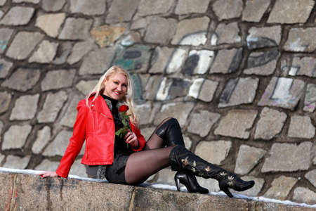 Beautiful blonde woman in red leather jacket with a rose