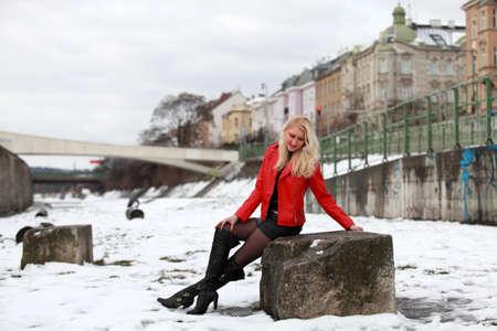 mini falda: Mujer rubia hermosa en la chaqueta de cuero rojo y mini falda