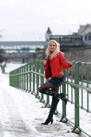 Schöne blonde Frau in roter Lederjacke und Minirock Standard-Bild