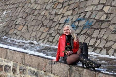 Schöne blonde Frau in der roten Lederjacke