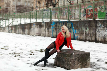 Beautiful blonde woman in red leather jacket and mini skirt