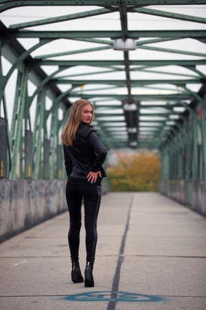 boot: Beautiful blonde girl in black leather jacket and leggings Stock Photo