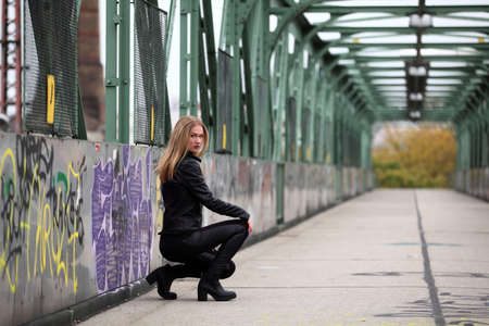 leather coat: Beautiful blonde girl in black leather jacket and leggings Stock Photo