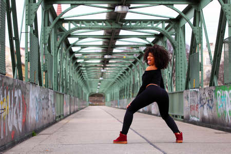 sexy dancer: Beautiful African girl with curly hair on a bridge