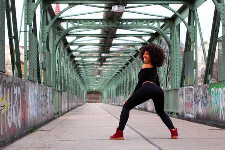 culo di donna: Bella ragazza africana con i capelli ricci su un ponte Archivio Fotografico