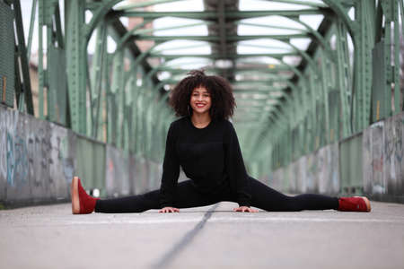 splits: Beautiful African girl with curly hair making splits