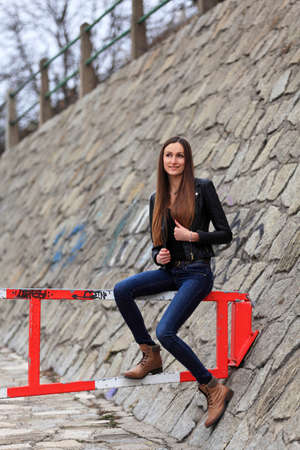 Beautiful girl with leather jacket, blue jeans and boots on the street