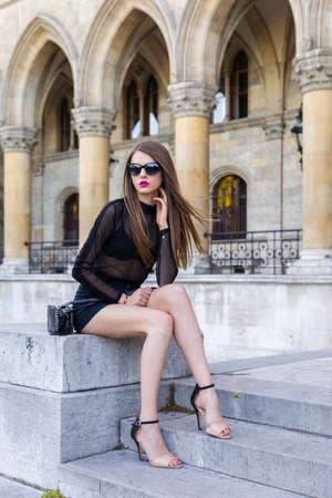 ミニのスカートと透明な上を身に着けている若い女性 写真素材