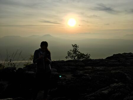 Silhouette scene of woman standing on the cliff mountain, sunset background