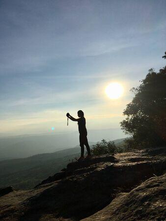 Silhouette of woman taking photo with smartphone at mountain peak on sunlight scene 版權商用圖片