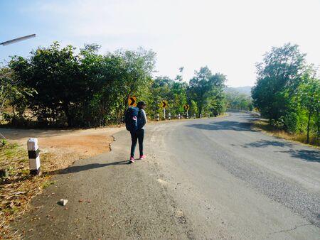 Viaggiatore donna con zaino che cammina sulla strada per un viaggio avventuroso