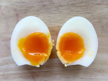 Two half of medium boiled eggs on wooden background, top view