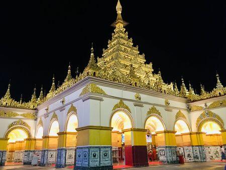 The golden architecture of Mahamuni temple in Mandalay city, Myanmar on night scene Banco de Imagens