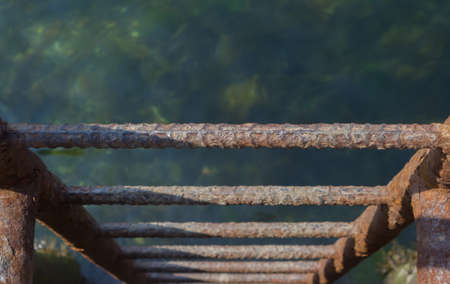 going down: A rusty ladder on the side of a dock going down into the water Stock Photo
