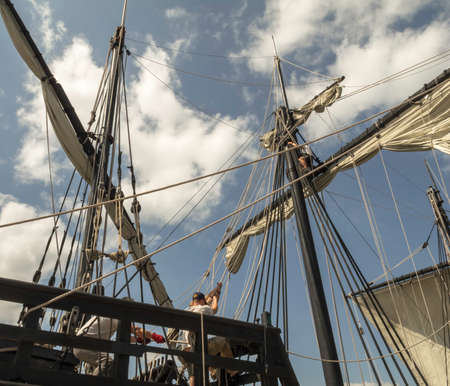 hard: Men manually pull on ropes o furl a sail on an antique tall ship Stock Photo