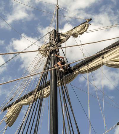 alongside: A man climbs into the rigging alongside the mast of a tall ship