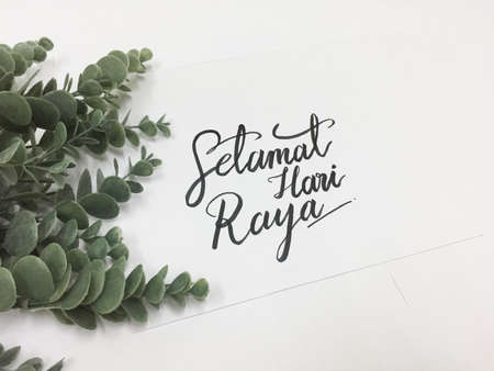 Card written Selamat Hari Raya (Happy Eid) on white paper against white background with eucalyptus plant Stock Photo