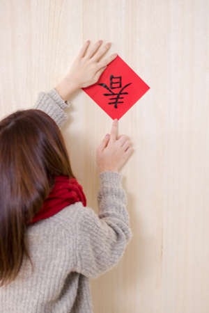 Beauty woman paste red envelope on the wall in chinese new year.