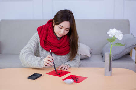 Smiling woman are writing Spring Festival couplets in the room in Chinese new year. 免版税图像