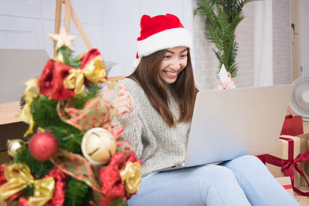 Woman hand holding credit card and doing shopping online near christmas tree at home.