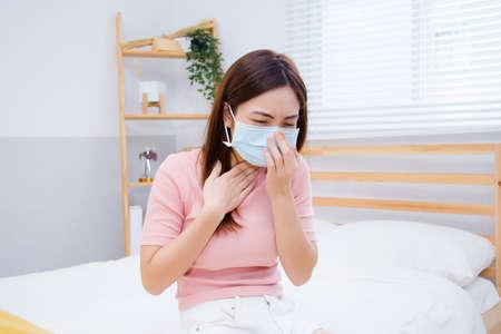 Frau leiden unter Husten mit Gesichtsmaskenschutz. Standard-Bild