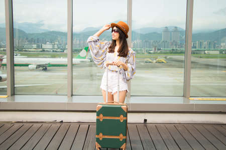 Young asian woman is holding luggage and looking forward to the trip at airport.