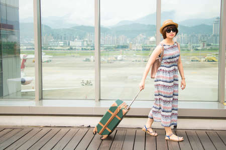 Young asian woman goes at airport at window with a suitcase waiting for plane.