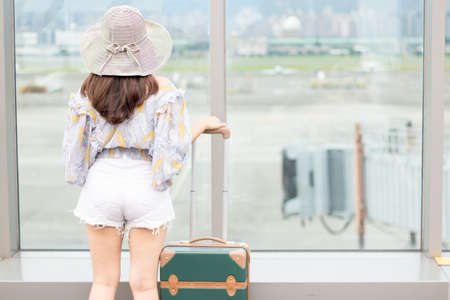Back view of woman who is holding a suitcase and standing at airport in Taiwan, travel concepts.