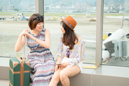 Two asian women using app on mobile phone, looking at screen of smart phone, texting, watching photos while traveling.