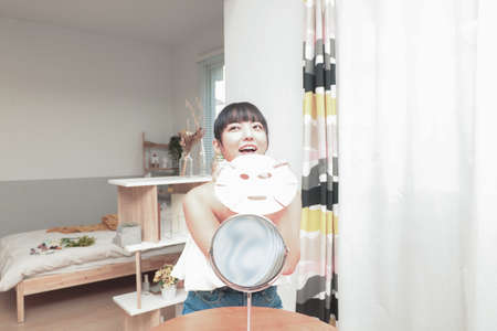 The beautiful asian woman doing the skin care with facial mask. 版權商用圖片