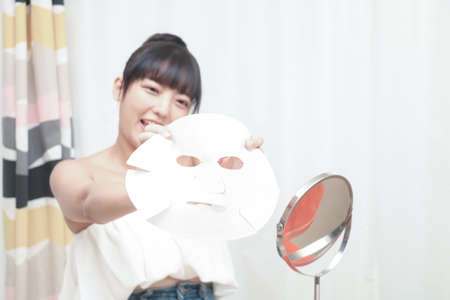 The beautiful asian woman doing the skin care with facial mask.