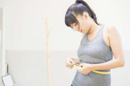 Asian woman is measuring her waistline. 免版税图像