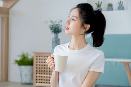 Young asia woman with ponytail in white t-shirt holding a cup of coffee or tea relaxing at home in the morning.