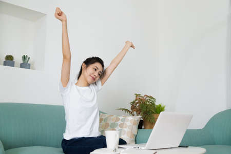 Happy relaxing woman stretching in front of computer at home. Smiling female reach out, put hands up sitting at laptop. People at work, remote work, studying, working online concept