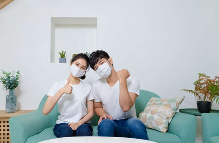 Asian couple wearing protective face mask and showing thumb up at home.