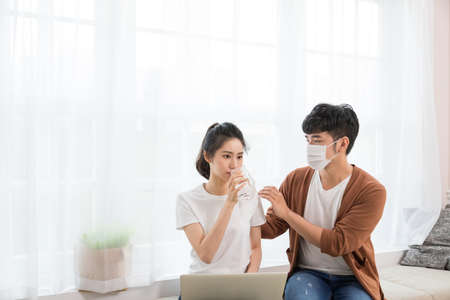 Couple wearing a protective face mask and woman working at home. But she got cold and flu, the man bringing her a hot drink and taking care of her.
