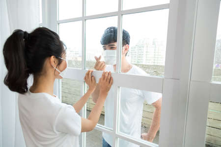 Man visiting girlfriend quarantined in home and showing heart gesture to her. 免版税图像