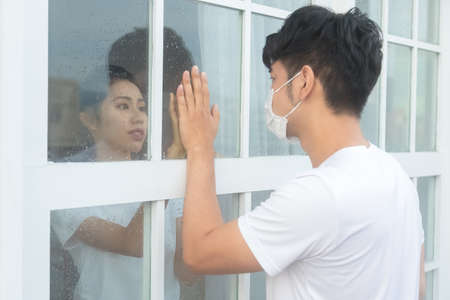 Man visiting girlfriend quarantined in home, touching hands through the window, main focus on woman. 免版税图像