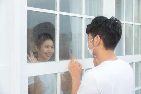 Man visiting girlfriend quarantined in home and greeting each other. 免版税图像